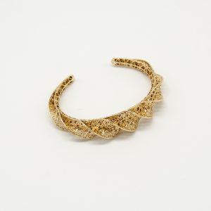 Bracciale dorato rigido con un particolare vortice. Il design rappresenta molto le tendenze di moda attuali, ed il prodotto è anche Made In Italy.