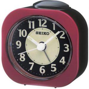 Orologio Sveglia analogico in plastica di colore nero e bordeaux con movimento al quarzo. Quadrante nero e bianco con lancette di colore bianco.