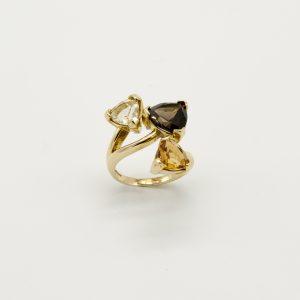 Anello per Donna a Marchio Peñaranda Jewels in Oro 750/1000. Ref.01990 L'anello è in Oro Giallo con incastonate 3 pietre di Forma Triangolare Le pietre sono dei Quarzi di colore Fumè,Citrino, Giallino chiaro L'anello è molto robusto e le pietre sono incastonate a griffe Il Peso è di 8,8 grammi circa totale, La Larghezza è di 23mm, La Misura è 15, ma a richiesta messa a misura gratuita presso il Nostro laboratorio Prodotto Made in Italy.