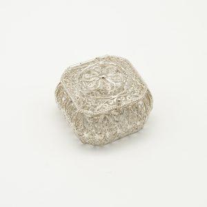 Scatola Portagioie in Argento 925/1000 a Marchio Peñaranda Jewels Ref. 14221 La Larghezza della scatola è di 50 mm, la profondità è 50 mm, e l'altezza è 31 mm. Il peso dell'argento è 26,3 grammi. La scatola è in Filigrana d'Argento ed è artigianale Solitamente viene utilizzata per contenere la coroncina del Rosario, ma potrebbe essere utilizzata anche come portagioie Il coperchio chiude ad incastro. Il prodotto è realizzato a Genova pertanto Made in Italy,